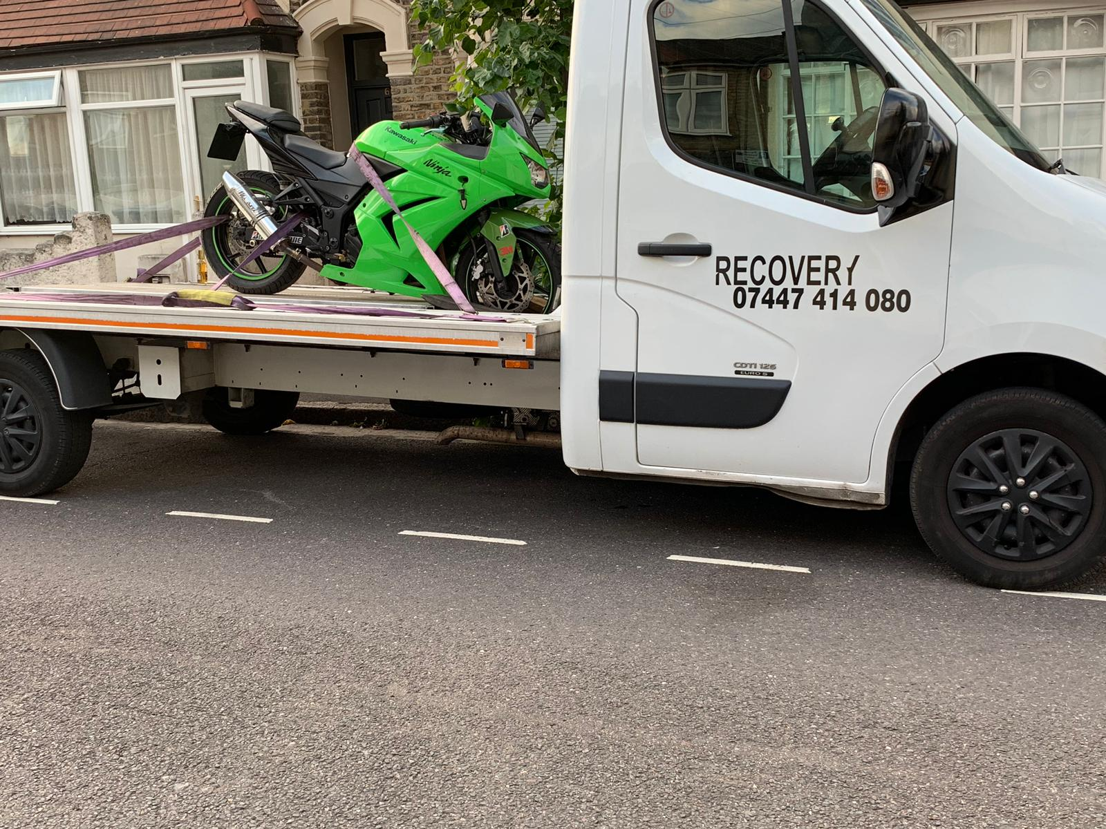 Tow truck recovering a broken down motorcycle in London
